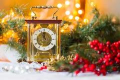 Weihnachts- und des neuen Jahresstillleben mit a mit einer Uhr, roten Beeren und Fichtenzweigen Lizenzfreie Stockbilder