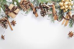 Weihnachts- und des neuen Jahreszusammensetzung Geschenkbox mit Band, Tannenzweige mit Kegeln, Sternanis, Zimt auf weißem Hinterg lizenzfreies stockbild