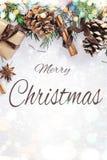 Weihnachts- und des neuen Jahreszusammensetzung Geschenkbox mit Band, Tannenzweige mit Kegeln, Sternanis, Zimt auf weißem Hinterg stockfotografie