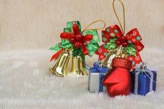 Weihnachts- und 26. Dezember-Konzept - Geschenk und nette Goldglocke auf Pelzboden Stockbilder