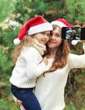 Weihnachts- und Technologiekonzept - Mutter und Kind, die Bildselbstporträt auf Smartphone togethe nehmen Stockbild