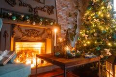 Weihnachtsabend durch Kerzenlicht klassische Wohnungen mit einem weißen Kamin, einem verzierten Baum, Sofa, große Fenster und Lizenzfreie Stockfotos