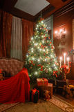 Weihnachtsabend durch Kerzenlicht klassische Wohnungen mit einem weißen Kamin, einem verzierten Baum, Sofa, große Fenster und Stockfoto
