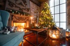 Weihnachtsabend durch Kerzenlicht klassische Wohnungen mit einem weißen Kamin, einem verzierten Baum, Sofa, große Fenster und Stockfotos