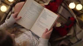 Weihnachtsabend, sitzt das Mädchen auf dem Bett, das mit einer Decke bedeckt wird und liest ein Buch, Weihnachtslichter, Familie stock video footage