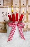 Weihnachtsabend: vier rote brennende Kerzen mit einem schäbigen weißen adve lizenzfreie stockfotos