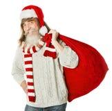 Weihnachtsalter Mann mit Bart im roten Hut, der Santa Claus-Tasche trägt Stockfotografie