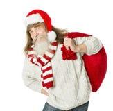 Weihnachtsalter Mann mit Bart im roten Hut, der Santa Claus-Tasche trägt Stockfotos