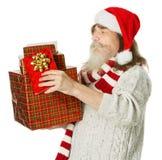 Weihnachtsalter Mann mit Bart in tragendem Präsentkarton des roten Hutes Lizenzfreie Stockfotografie