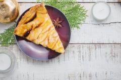 Weihnachtsapfelkuchen auf Platte mit weißen Kerzen und Baum brunche Stockfoto