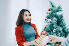 Weihnachtsasiats-Paare Ein gutaussehender Mann, der ihre Freundin/wif gibt stockbild
