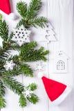 Weihnachtsaufbau auf einem weißen Hintergrund Weihnachtsbaumaste, Santa Claus-Hut, dekorative Schneeflocken und ein kleines Haus  Lizenzfreie Stockfotos