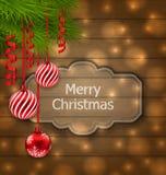 Weihnachtsaufkleber mit Bällen und den Tannenzweigen auf hölzerner Beschaffenheit mit lizenzfreie abbildung