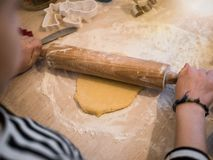 Weihnachtsbäckerei: Wenig Mädchenrollenplätzchenteig stockbild