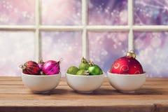 Weihnachtsbälle auf Holztisch über träumerischem Hintergrund des Fensters Lizenzfreie Stockfotografie