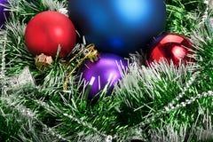 Weihnachtsbälle in der grünen Girlande Lizenzfreie Stockbilder