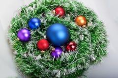 Weihnachtsbälle in der grünen Girlande mit Weihnachtsglocken Stockfotografie