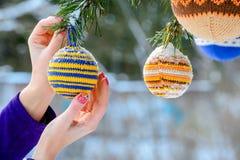 Weihnachtsbälle, die an den Kiefernniederlassungen umfasst mit Schnee hängen Stockbild