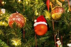 Weihnachtsbälle, die in einem Weihnachtsbaum hängen Stockfotografie