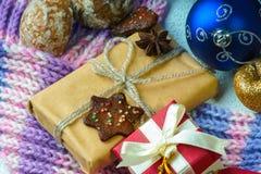 Weihnachtsbälle, Geschenkbox, Winterschal, Plätzchen und Trockenfrüchte Stockfoto