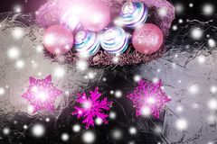 Weihnachtsbälle im purpurroten Korb auf schwarzem Hintergrund Schneeflocken auf Blau Lizenzfreies Stockbild