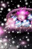 Weihnachtsbälle im purpurroten Korb auf schwarzem Hintergrund Schneeflocken auf Blau Stockbild