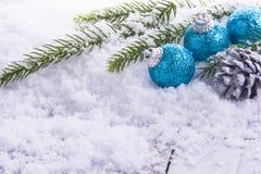 3 Weihnachtsbälle, Kiefernkegel und grüne Niederlassung auf Schnee Stockfotografie
