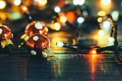 Weihnachtsbälle mit einer Girlande auf einem Holztisch Abstraktes Hintergrundmuster der weißen Sterne auf dunkelroter Auslegung S Stockfotografie