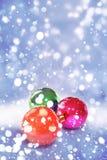 Weihnachtsbälle mit fallendem Schnee Stockbild