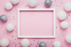Weihnachtsbälle, Paillette und Bilderrahmen auf stilvoller rosa Tischplatteansicht Art und Weisehintergrund Flache Lage Parteimod lizenzfreie stockfotografie