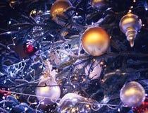 Weihnachtsbälle und -dekorationen mit einer hellen Girlande auf dem Weihnachtsbaum stockfoto