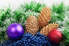Weihnachtsbälle und -kegel mit grüner Girlande Stockbilder