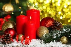 Weihnachtsbälle und -kerzen auf hölzernem Hintergrund Stockfoto