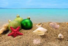Weihnachtsbälle und -oberteile auf Sand mit Sommermeer Lizenzfreies Stockbild