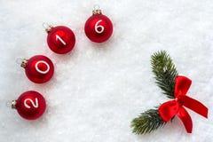 Weihnachtsbälle 2016 und Tannenzweig auf Schneehintergrund mit Raum für Ihren Text Lizenzfreie Stockfotos