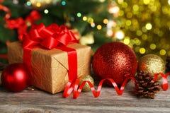 Weihnachtsbälle und Weihnachtsgeschenk auf hölzernem Hintergrund Lizenzfreie Stockfotografie
