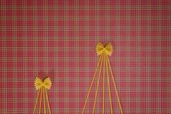 Weihnachtsbäume gemacht von den Teigwaren auf rotem quadratischem Hintergrund Flache Lage Beschneidungspfad eingeschlossen Kopier Lizenzfreie Stockfotos