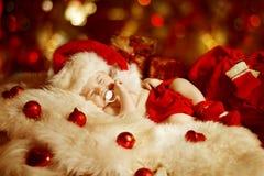 Weihnachtsbaby, neugeborenes Kind, das als Weihnachtsgeschenk in Santa Hat schläft Lizenzfreie Stockfotografie