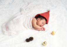 Weihnachtsbaby in Santa Hat, asiatisches Baby im Weihnachtshut schläft Lizenzfreies Stockbild