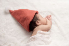 Weihnachtsbaby in Santa Hat, asiatisches Baby im Weihnachtshut schläft Stockfotos
