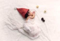 Weihnachtsbaby in Santa Hat, asiatisches Baby im Weihnachtshut schläft Stockbild