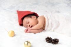 Weihnachtsbaby in Santa Hat, asiatisches Baby im Weihnachtshut schläft Stockfoto
