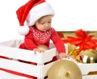 Weihnachtsbabykind in Sankt-Hut, der Goldkugeldekoration n hält Stockfotografie