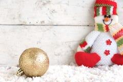 Weihnachtsball auf dem Schnee mit Schneemannhintergrund Stockfotos