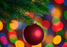 Weihnachtsball auf dem Tannenzweig auf dem Lichterkette-Hintergrund Stockbilder