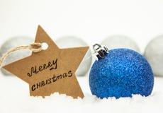 Weihnachtsball im Blau auf weißem Schnee und ein Stern mit den Aufschrift frohen Weihnachten, in den silbernen Bällen des Hinterg stockfotos