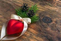 Weihnachtsball mit einem Bandherzen Stockfoto