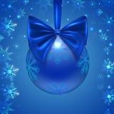 Weihnachtsball mit einem blauen Bogen, Schneeflocken, lizenzfreies stockfoto