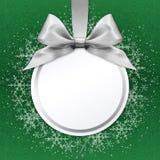 Weihnachtsball mit silbernem Satinbandbogen auf Grün Stockbild