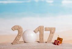 Weihnachtsball und die Aufschrift 2017 im Sand Stockfotos